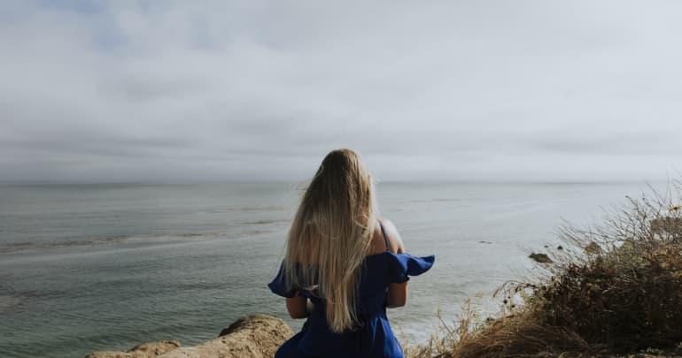 A woman sitting alone at a beach