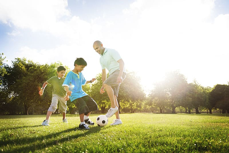 Child and adult playing soccer