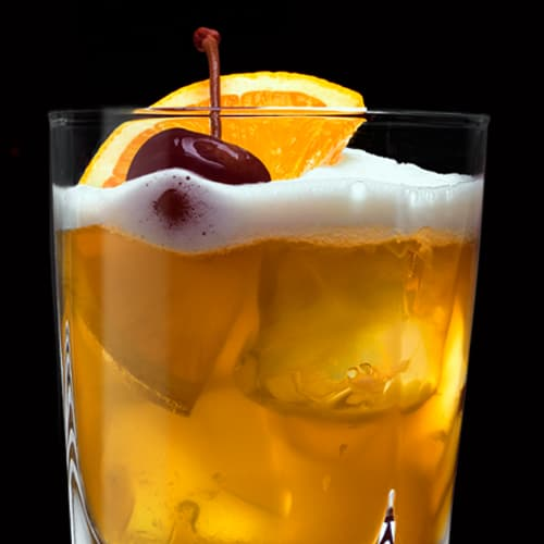 Jack Sour Cocktail served with orange slice and cherry