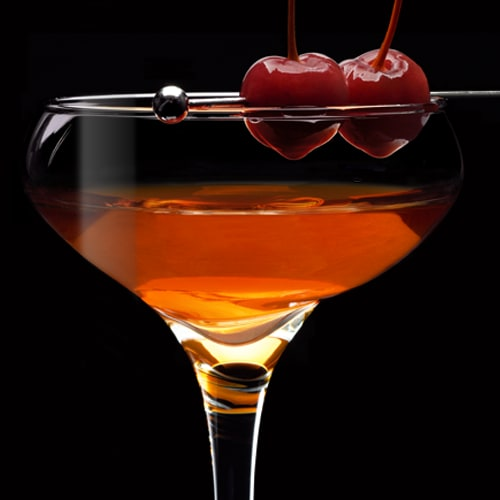 Gentleman's Manhattan Cocktail served with cherries