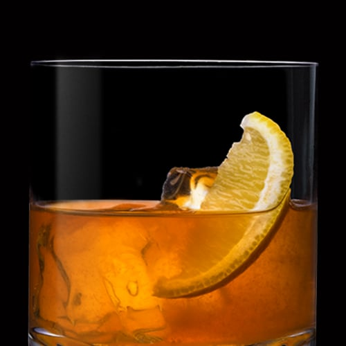 Gentleman's Sour Cocktail served with lemon wedge