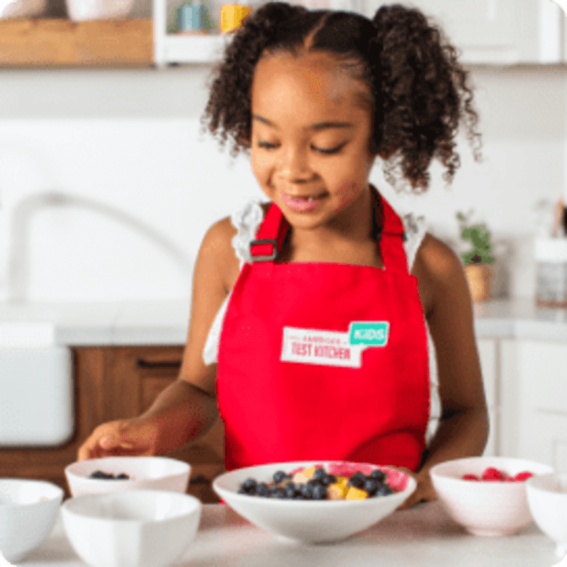 young girl wearing red apron stands at counter with bowls of berries
