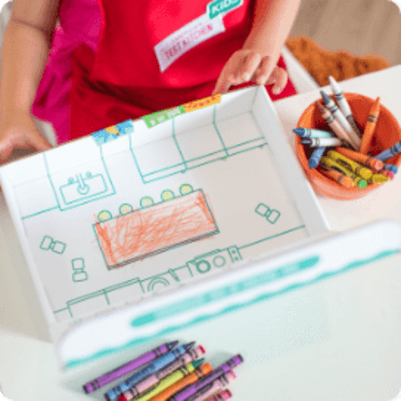 overhead view of child drawing a picture with crayons
