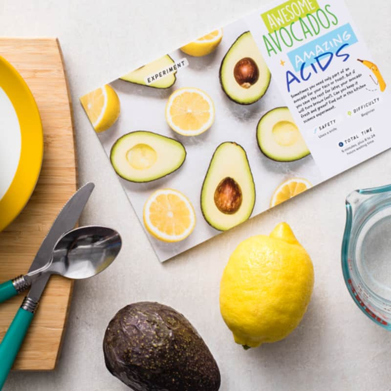 recipe card on cutting board next to an avocado and a lemon