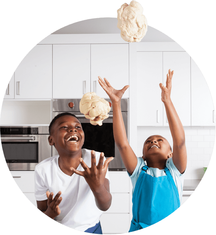 Two boys laughing and throwing dough into the air