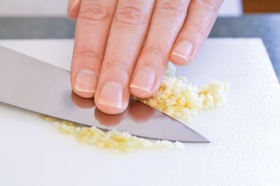 dragging knife blade across minced garlic to make paste