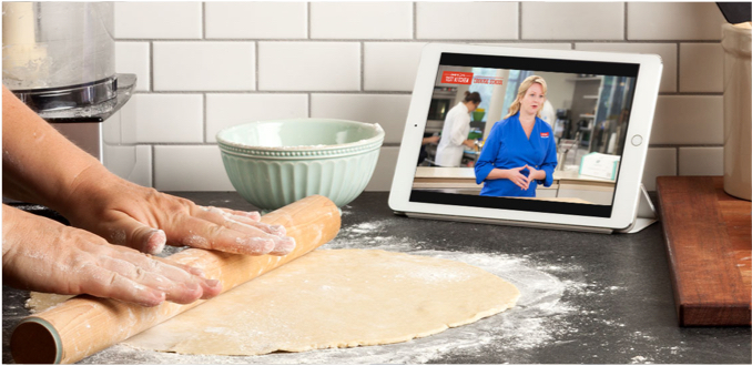 rolling a dough while viewing onlinecookingschool content on a tablet