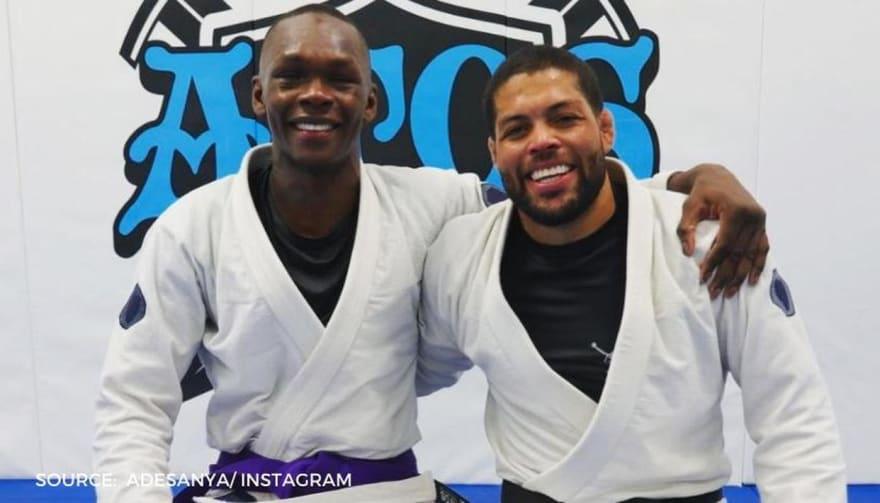 Israel Adesanya receives his jiu-jitsu purple belt