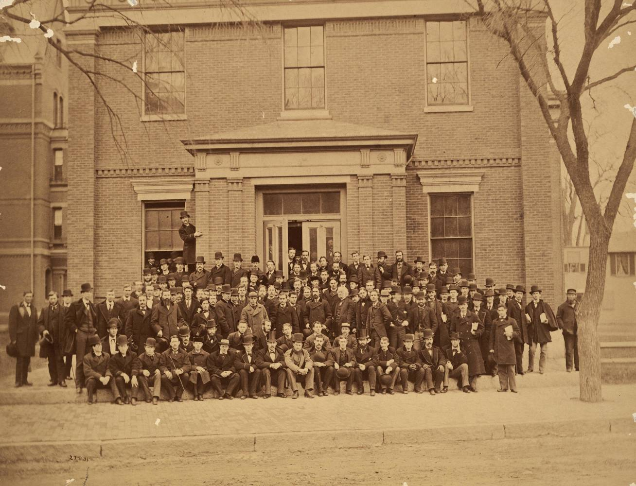 Historical photo of HLS Class of 1877. Students wearing black jackets and top hats posing for photo outside in front of a building