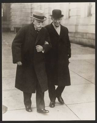 Two men in black coats and hats taking a stroll outside arm in arm