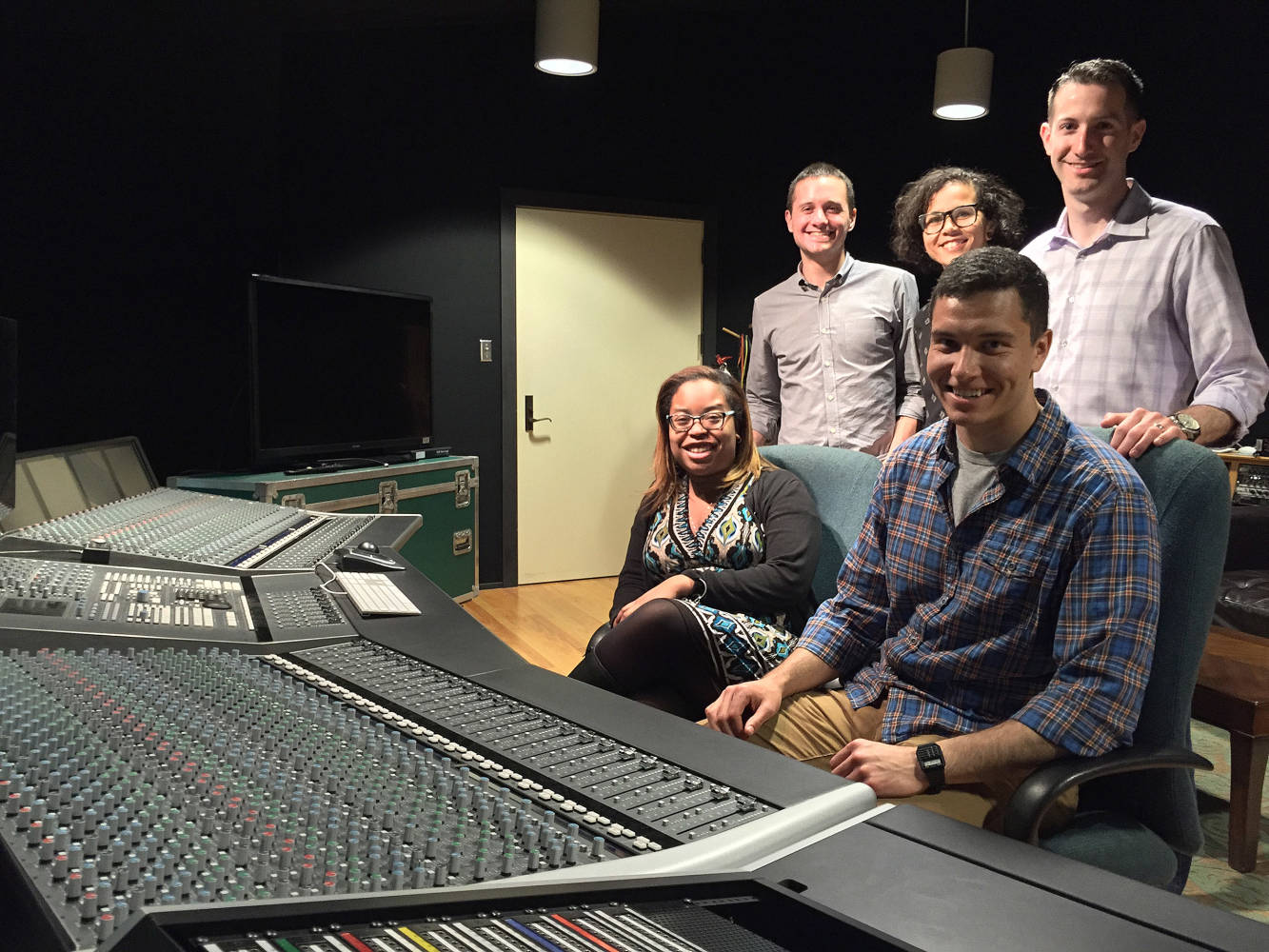 Group of five students enjoying time together in a recording studio