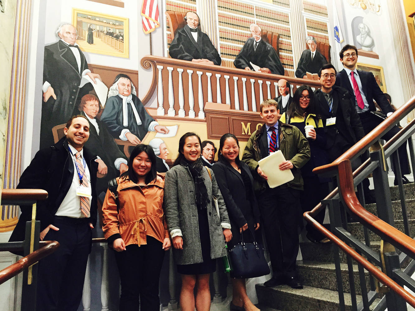 Students pose for photo on stairs after volunteering with Volunteer Lawyers Project at the Massachusetts Continuing Legal Education center
