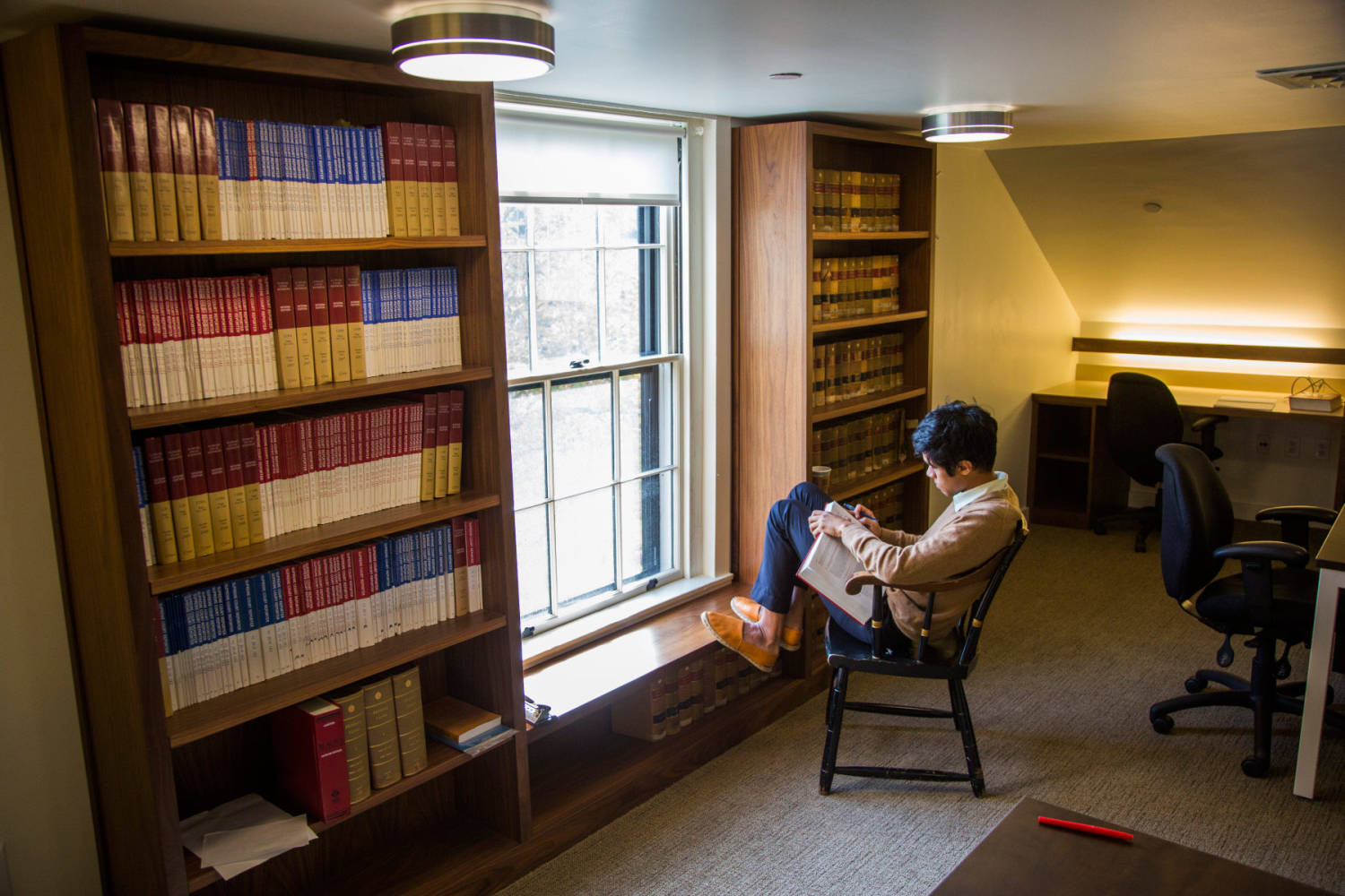Student studies in front of a window in a study room