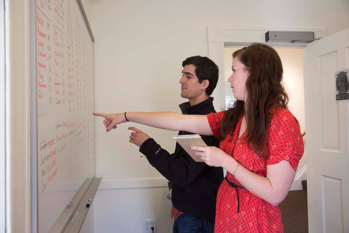 Student gestures to whiteboard while other student investigates