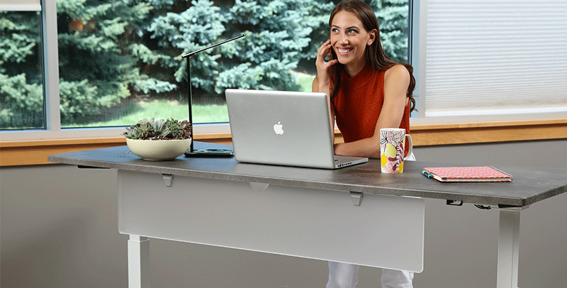 Woman standing at SmartMoves Adjustable Height Desk