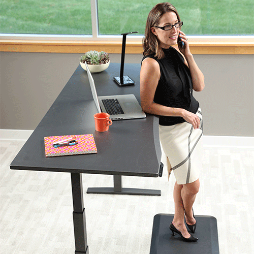 Woman standing at 72 inch Adjustable Height Desk working in office