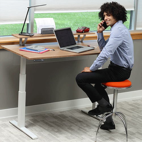 Man standing at 48 inch Adjustable Height Desk working from home
