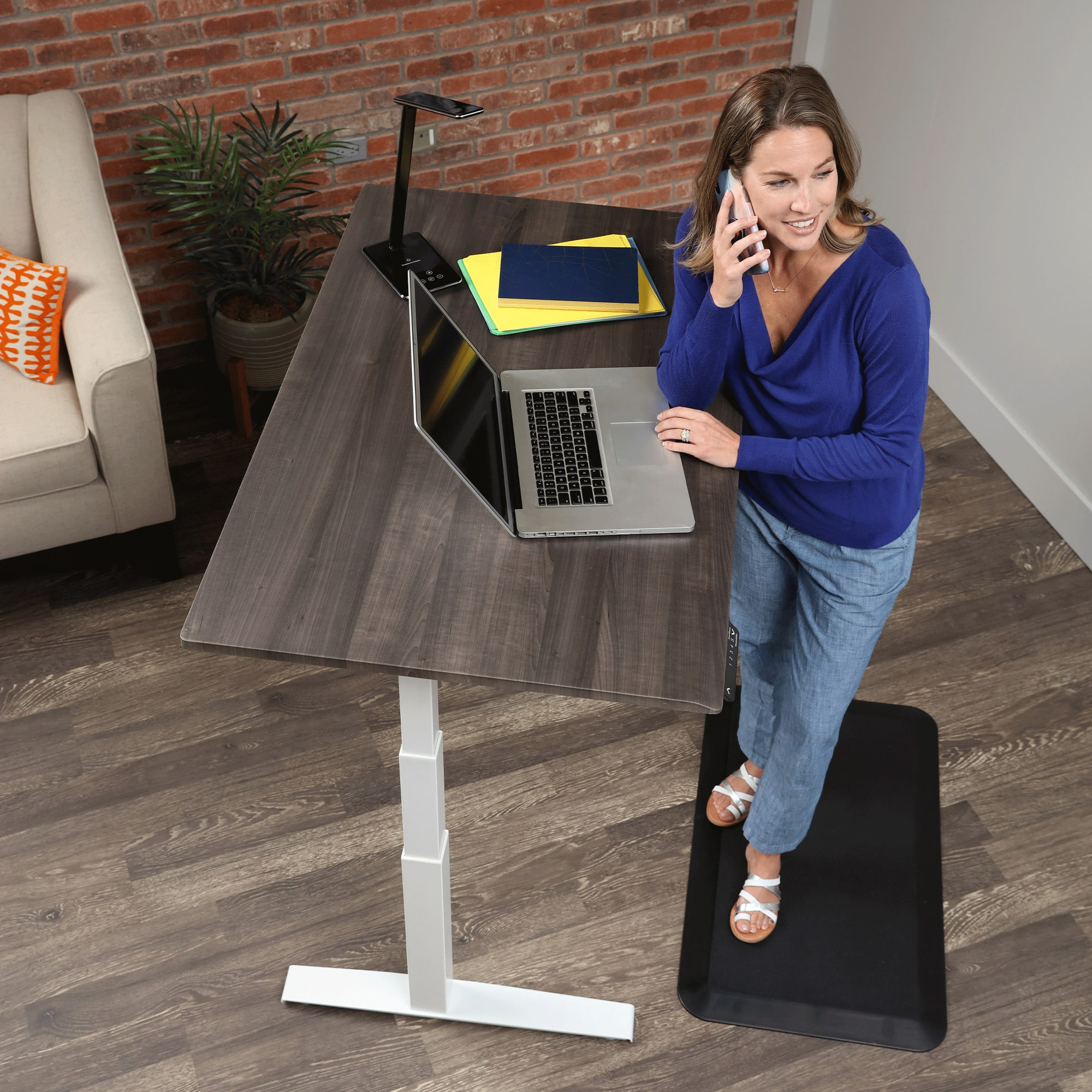 Woman in blue working from home on a SmartMoves Adjustable Height Desk