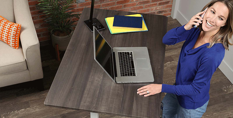 Woman working from home standing at SmartMoves Adjustable Height Desk