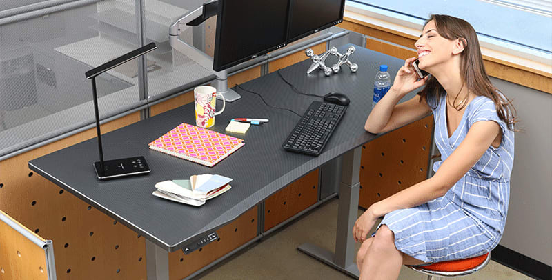 Woman On Stool At SmartMoves Adjustable Height Desk