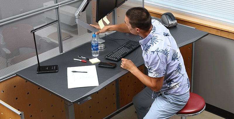Man adjusting monitor arm at SmartMoves Adjustable Height Desk