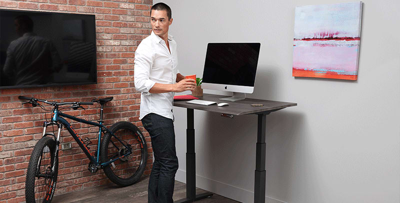 Man Standing at SmartMoves Adjustable Height Desk