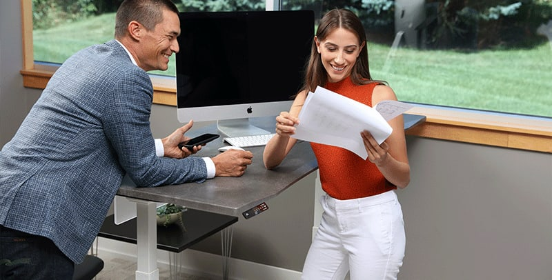 Man and Woman Standing at SmartMoves Adjustable Height Desk Together