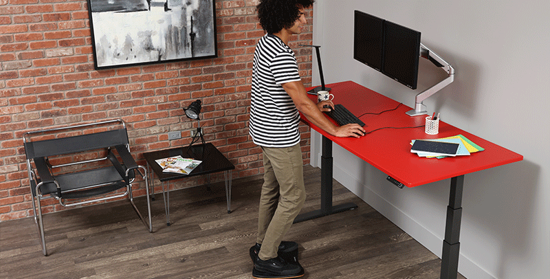 Man working from home standing at SmartMoves Adjustable Height Desk