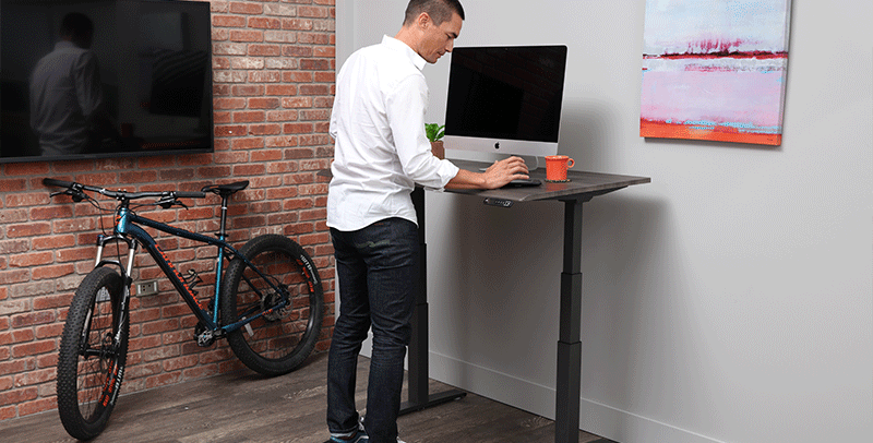 Man Standing on Fitness Board on SmartMoves Adjustable Height Desk