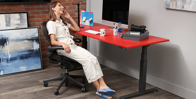 Woman sitting at Hot Rod Red SmartMoves Adjustable Height Desk