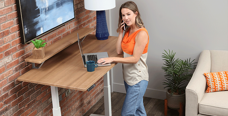 Woman standing at SmartMoves Adjustable Height Desk working from home