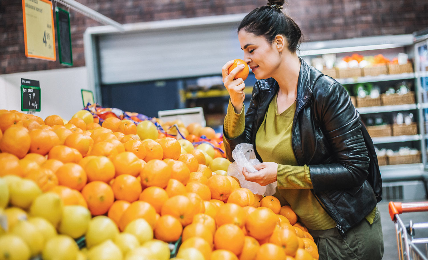 woman smelling oranges while shopping for groceries