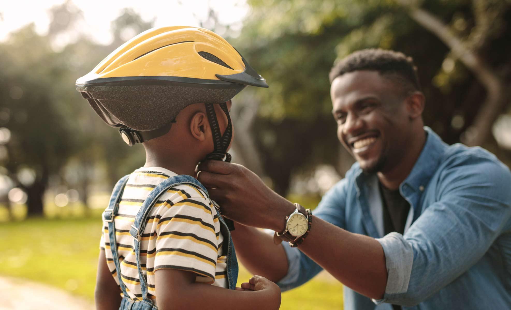 dad helping son with bike helmet