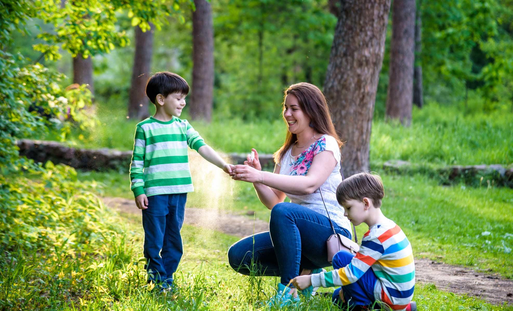 mother putting bug spray on child