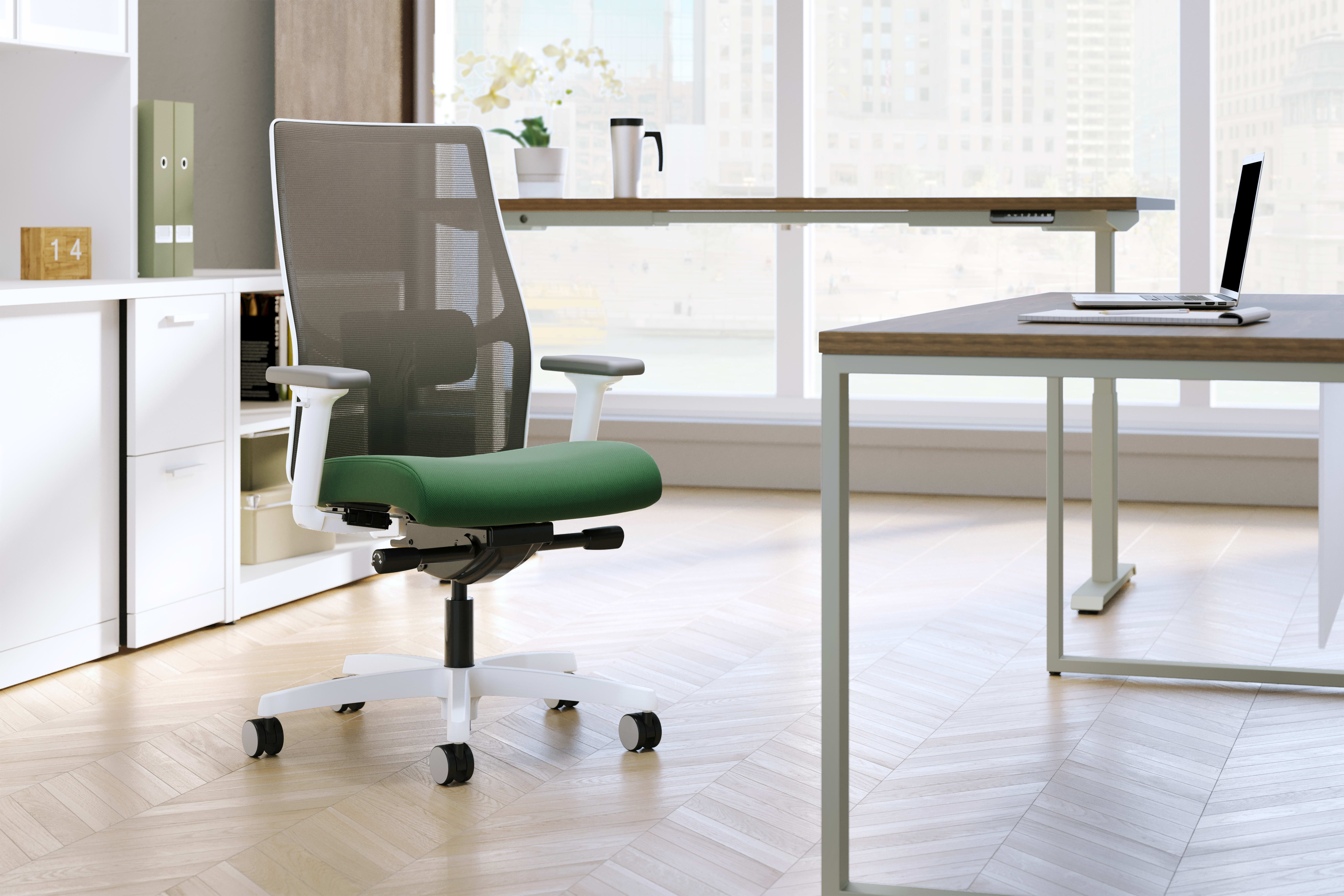 Ignition mesh-back chair with white frame and green fabric seat in an office setting.