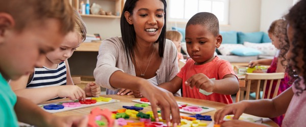 A preschool teacher is someone who helps young children prepare for kindergarten through play, interactive activities, and games.