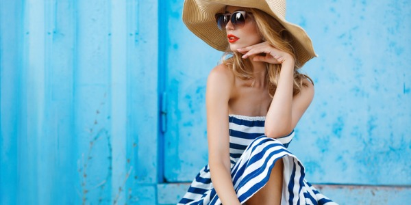 A model posing for the camera in a big hat, sunglasses, and a sundress.