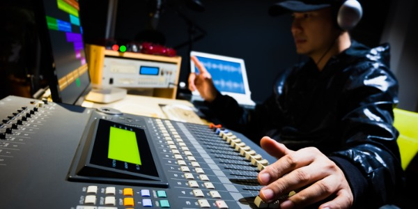 A live sound engineer is someone who blends and balances multiple sounds at a live event by using a mixing console, pre-recorded material, voices and instruments.