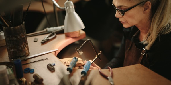 A jeweler is an artisan who uses metals, gems and other materials to create adornments like bracelets, earrings, rings, and necklaces.