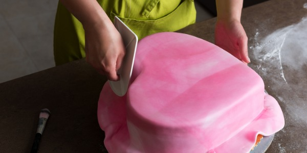 Cake designers manipulate the frosting or fondant to create a custom designed cake based on instructions provided by the customer.