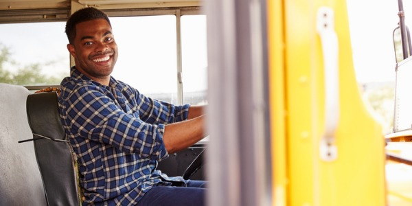 A bus driver transports people between a variety of places including work, school, shopping, and across country.
