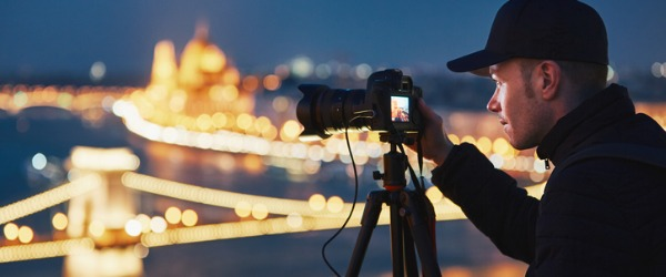 Landscape photographer taking a picture of city lights.