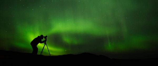 A professional photographer taking a picture of the northern lights.