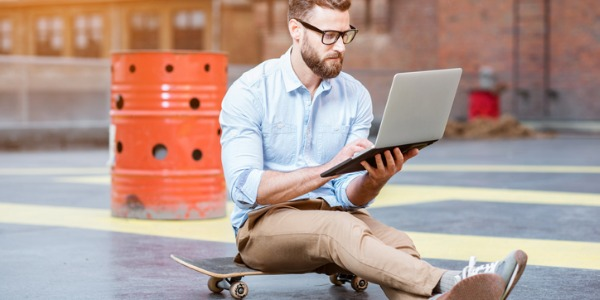 Young entrepreneur sitting on a skateboard and looking at his computer.