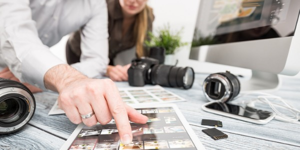 Art director looking at various photographs to use in a magazine layout.