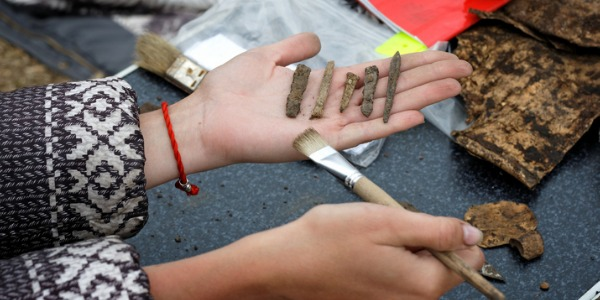 Archaeologist holds in his hand several different ancient arrowheads.