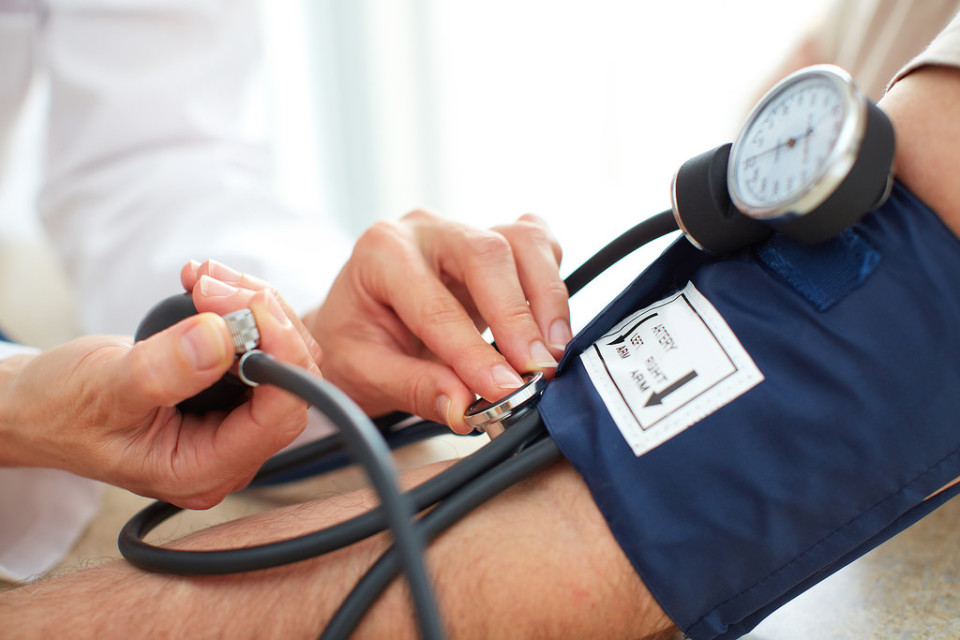 A photo of a doctor checking blood pressure.