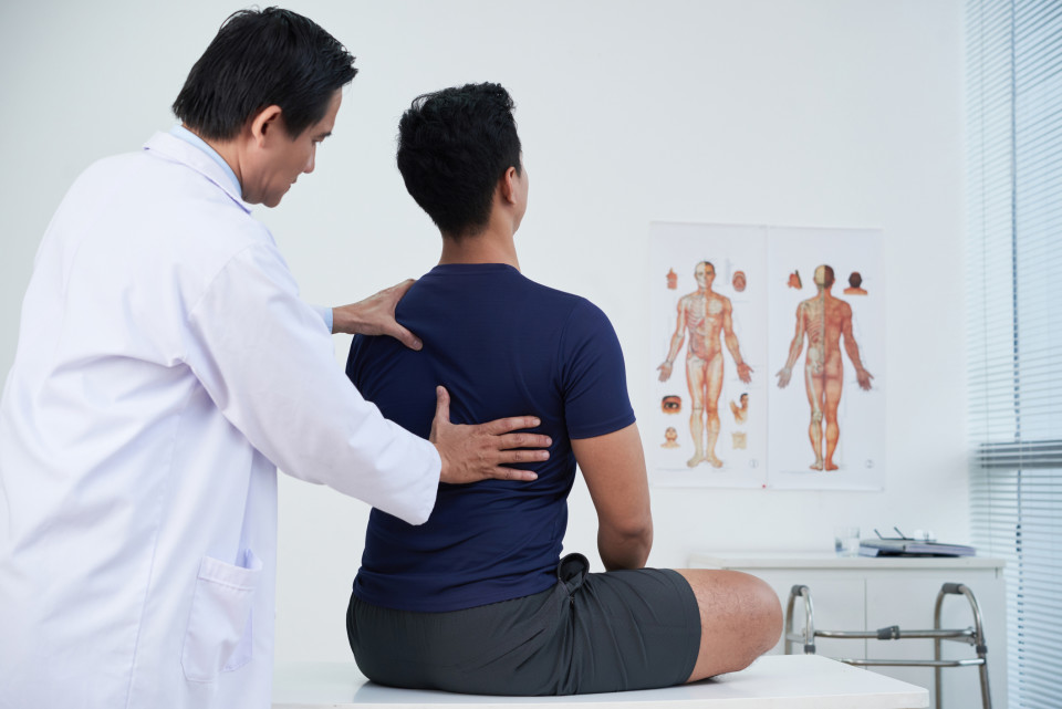 A photo of a chiropractor examining a patient.