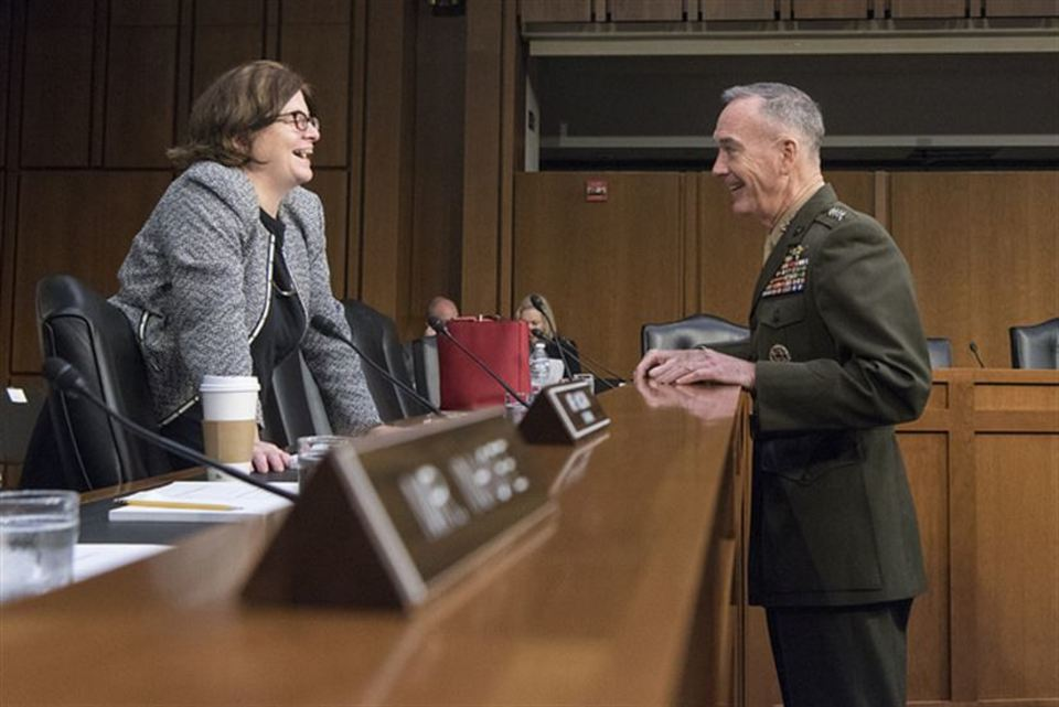 A photo of a forensic psychologist meeting with an army general in a courtroom.