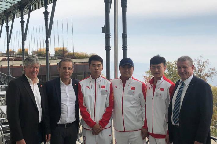 Die Projektverantwortlichen mit drei chinesischen Eishockeyspielern.